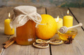Jar of honey, oranges and candles on wooden table — Stock Photo