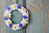 White wicker wreath decorated with cornflowers — Stock Photo