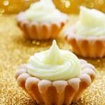 Tiny cupcakes on golden background — Stock Photo #50624339