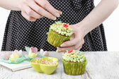 Woman decorating cupcakes — Stock Photo