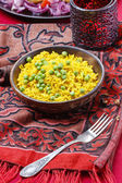 Indian cuisine: bowl of yellow rice with green peas — Stock Photo
