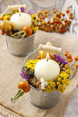 Candle holder decorated with autumn flowers and other plants. — Stock Photo