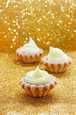 Tiny cupcakes on golden background — Stock Photo