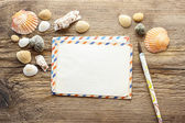 Writing a letter from holiday. Seashelles on a wood — Stock Photo