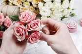 Florist at work. Woman making bouquet of pink roses — Stockfoto