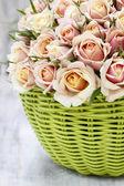 Bouquet of roses in a green wicker basket — Stockfoto