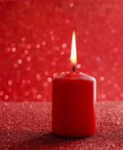 Red candle. Red glittering christmas lights. Blurred abstract ba — Foto Stock