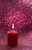 Red candle. Red glittering christmas lights. Blurred abstract — Stock Photo