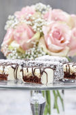 Chocolate and marzipan cakes on glass cake stand.  — Stock Photo