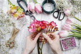 Florist at work. Woman making bouquet of spring freesia flowers — Stock Photo