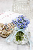 Bouquet of forget-me-not flowers in glass vase, stack of vintage — Stockfoto