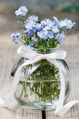 Bouquet of forget-me-not flowers in glass vase — Stock Photo