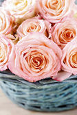 Pink roses in turquoise wicker basket — Stock Photo