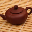 Brown teapot on the bamboo table-cloth — Stock Photo #24367087