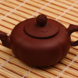 Brown teapot on the bamboo table-cloth — Stock Photo