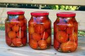 Tre glas burkar röda tomater på träbänk — Stockfoto