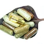 Herbal capsules in basil leaf — Stock Photo #22630979
