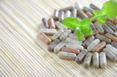 Herbal capsules with mint leaves — Stock Photo