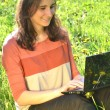 Beautiful attractive brunette girl is sitting on a meadow with laptop — Stock Photo