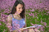 Beautiful attractive brunette girl reading a book on gorgeous meadow full of wild flowers — Стоковое фото