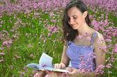 Piękny atrakcyjny brunetka dziewczyna czytając książkę na wspaniały łąka pełna kwiatów dzikiego — Zdjęcie stockowe