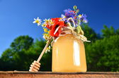 Jar full of delicious fresh honey honey dipper and wild flowers in apiary against blue sky — Stock Photo