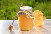 Wooden dipper, honeycomb and jar full of delicious fresh honey in apiary — Stock Photo
