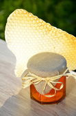 Honeycomb and jar full of delicious fresh honey in apiary — Stock Photo