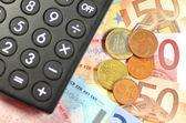 Euro banknotes, coins and calculator — Stock Photo