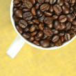 White coffee cup full of coffee beans  — Stock Photo