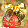 Christmas decoration, red Christmas ball with golden bow in bokeh background — Stock Photo