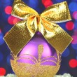 Christmas decoration, violet Christmas ball with golden bow in bokeh background — Stock Photo