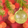 Christmas decoration, golden Christmas ball hanging on spruce twig against bokeh background — Stock fotografie