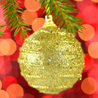 Christmas decoration, golden Christmas ball hanging on spruce twig against bokeh background — Stock Photo #36473855