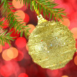 Christmas decoration, golden Christmas ball hanging on spruce twig against bokeh background — Stock Photo #36473865