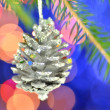 Christmas decoration, Christmas silver cone hanging on spruce twig against bokeh background — Stock Photo #36474011