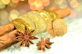 Christmas spices, cinnamon sticks, anise stars and walnut on bokeh background — Foto Stock
