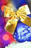 Christmas decoration, blue Christmas ball with golden bow in bokeh background — Stock Photo
