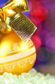 Christmas decoration, golden Christmas ball with golden bow in bokeh background — Stock Photo