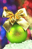 Christmas decoration, green Christmas ball with golden bow in bokeh background — Stock Photo