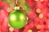 Christmas decoration, Christmas ball hanging on spruce twig against bokeh background — Stock Photo
