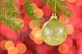 Christmas decoration, golden Christmas ball hanging on spruce twig against bokeh background — Stock Photo