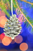 Christmas decoration, Christmas silver cone hanging on spruce twig against bokeh background — Stock Photo