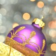 Christmas decoration, violet Christmas ball against bokeh background — Stock Photo