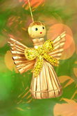 Christmas decoration, golden angel made of straw against bokeh background — Stock Photo