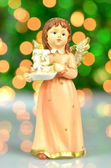 Christmas decoration, figure of angel holding a candle against bokeh background — Stock Photo