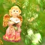 Christmas decoration, figure of little angel singing carols against bokeh background — Stock Photo #36915551