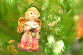 Christmas decoration, figure of little angel singing carols against bokeh background — Stock Photo