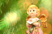Christmas decoration, figure of little angel singing carols against bokeh background — Stock Photo