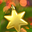 Christmas decoration, golden Christmas star ball hanging on spruce twig against bokeh background — Stock Photo #36932351